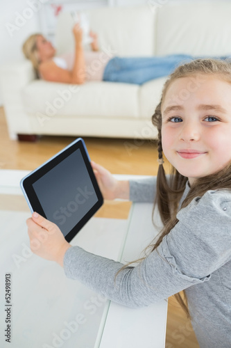 Smiling girl using tablet computer while mother is reading