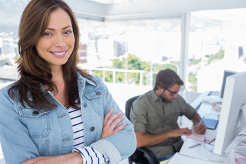 Woman smiling in creative office with arms crossed