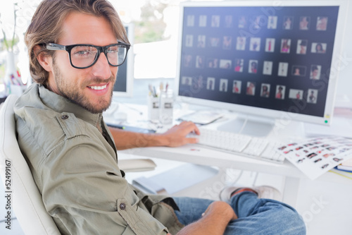 Photo editor turning and smiling at his desk
