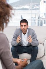 Upset man speaking to a therapist