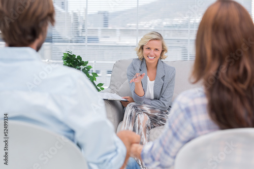 Smiling psychologist talking to a couple