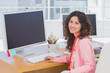 Woman working in a creative office and smiling at camera