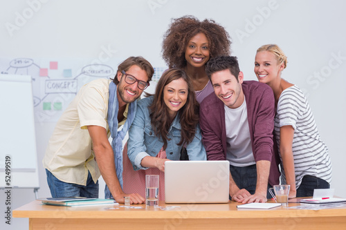 Creative team standing at desk with laptop