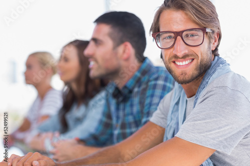Creative team sitting in a line with one man smiling