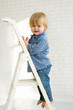 Smiling little boy standing on the step of a ladder