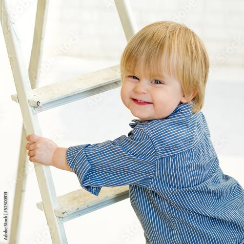 Happy little boy climbing the ladder