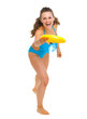 Portrait of happy young woman in swimsuit throwing flying disc