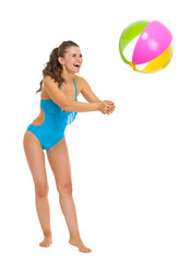 Smiling young woman in swimsuit playing with beach ball