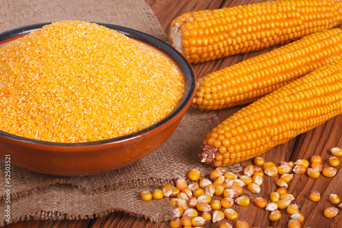 Corn groats in a bowl, whole grain and cob on a wooden table.