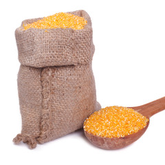 Corn groats in a bag and a wooden spoon isolated on a white
