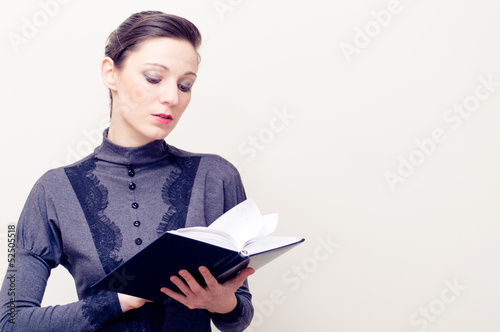 Young beautiful woman in vintage dress reading bible