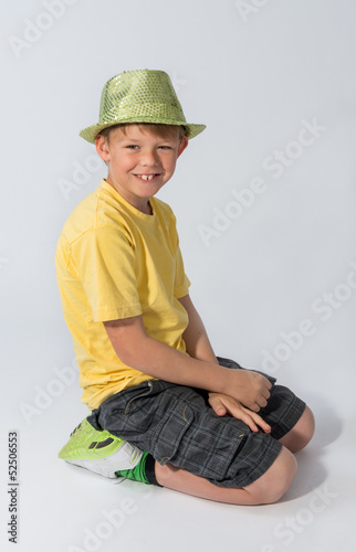 Young boy kneeling wearing a hat
