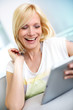 Smiling blond girl looking at tablet screen