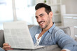Relaxed guy at home reading newspaper