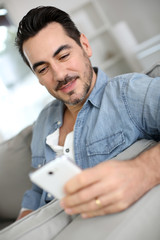 Smiling middle-aged man using smartphone