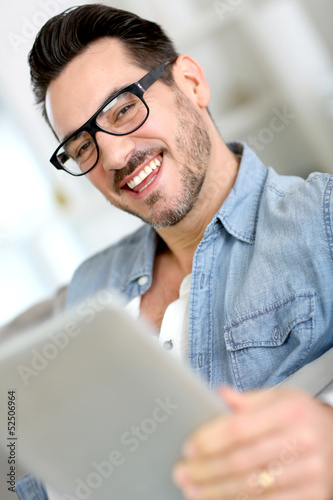 Middle-aged guy using digital tablet at home