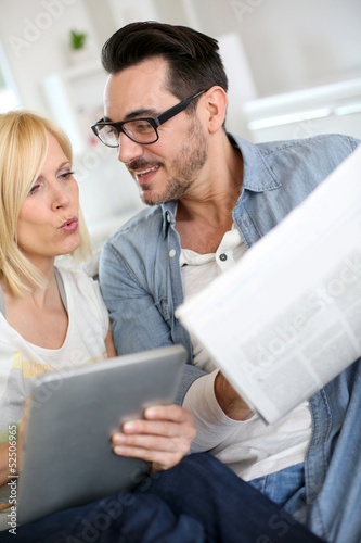 Couple reading news on both internet and paper