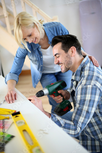 Couple installing furniture in new house