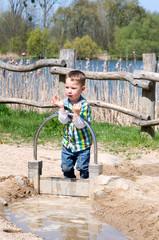 Kleiner Junge spielt mit Waeer am Strand