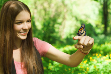 butterfly sitting on the finger of a young woman in the park