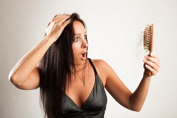 Frau blickt schockiert auf ihre Haarbürste