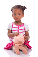 Cute little black girl holding a smiling piggy bank - African ch