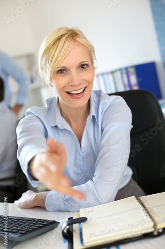 Businesswoman giving handshake to client