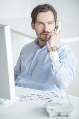 Busy businessman talking phone at his desk