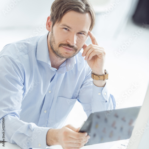 Young hansome businessman sitting at the desk