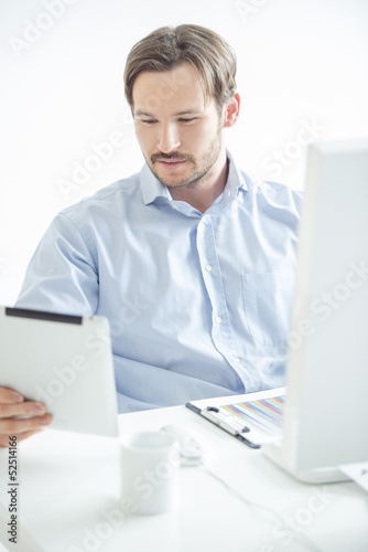 Businessman checking his work at tablet
