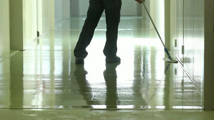 Un uomo asciuga il pavimento