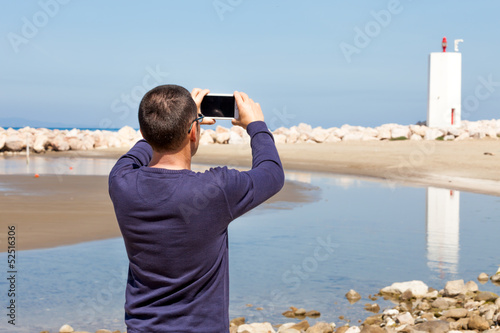 Man Taking Pictures Of Lighthouse