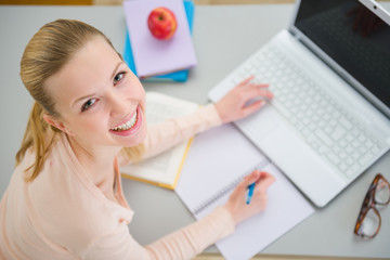 Smiling teenager girl studying in kitchen