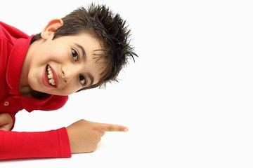Smiling young boy pointing his finger to something