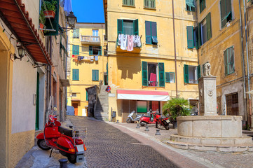 Small plaza among colorful houses in Ventimiglia, Italy.
