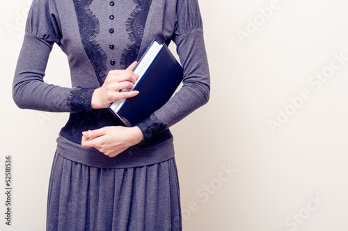 Young beautiful woman in gray vintage dress holding bible