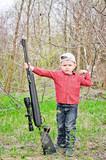 Cute little boy holding a big rifle