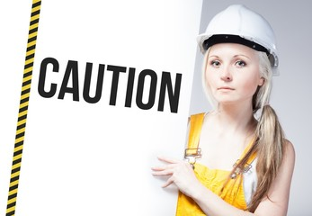 Worker holding caution sign on information board