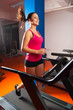 Beautiful smiling girl running on treadmill in the gym