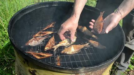 man hand take fresh smoked fish from smokehouse