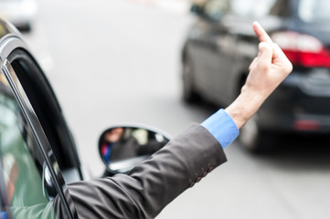 Man showing middle finger from car window