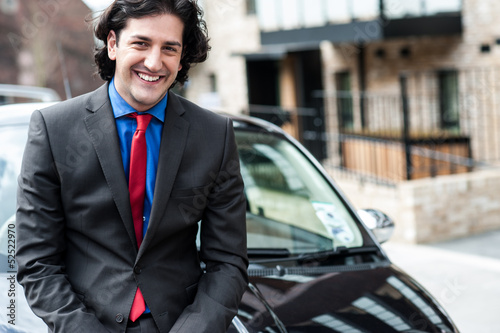 Handsome corporate man posing in front of his new car