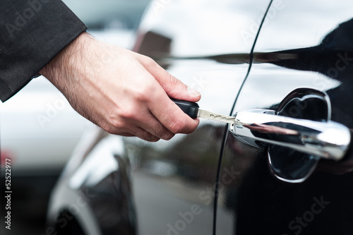 Man inserting car key into the door lock