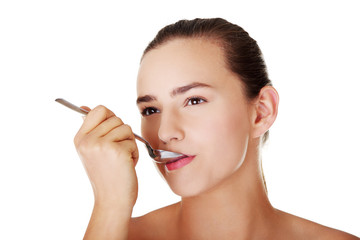 Teen girl with spoon in mouth.