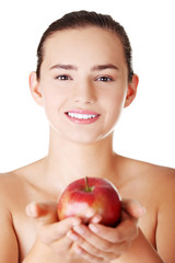 Happy fit teen woman with apple