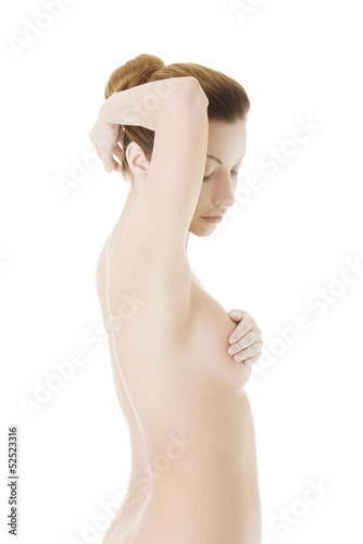 Caucasian adult woman examining her breast