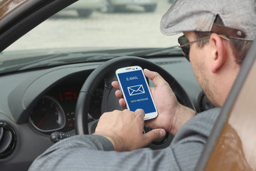Businessma checking email in a car
