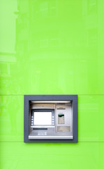 ATM machine in green wall shining in sun.