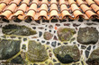 Tiled roof and wall decorated with stones.