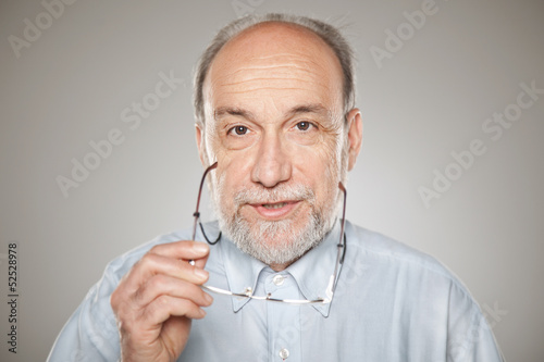 Portrait of old man taking glasses